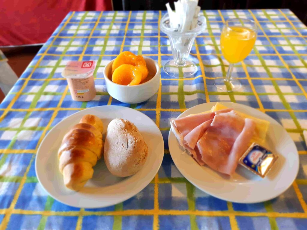 パン2個とハム、チーズ、桃の砂糖漬け、オレンジジュースのHotel Mira Serraの朝食