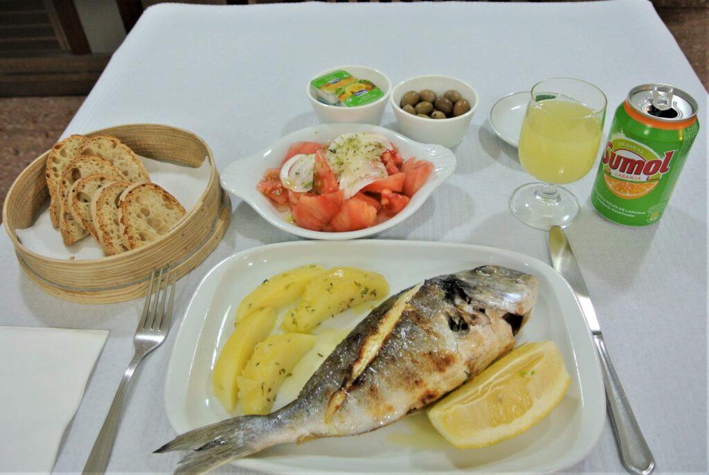 ふっくらした焼き魚とパン、トマトのサラダ、付け合わせのオリーブとオレンジジュース
