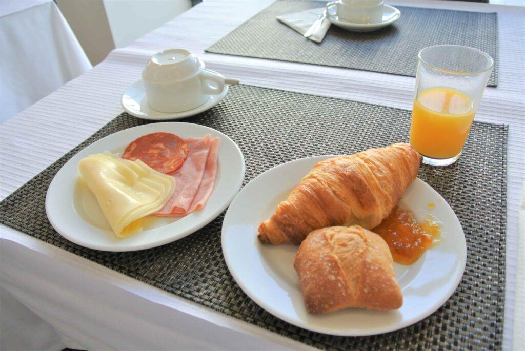 ハム、チーズ、2種類のパンとオレンジジュースのHotel Beira Rioの朝食