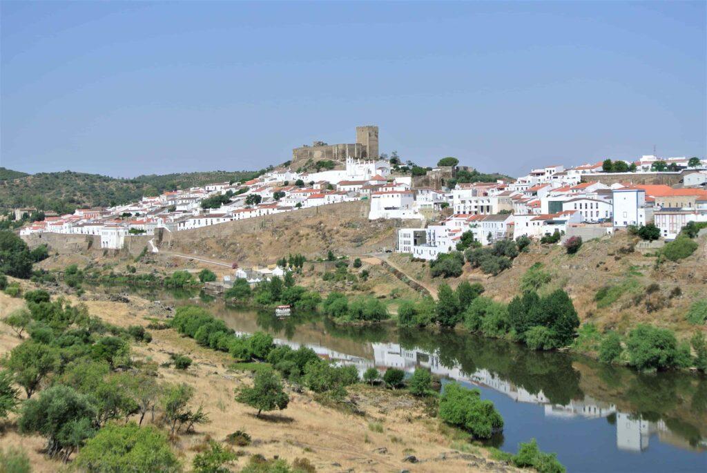 川の奥にメルトラ市街と丘の上のメルトラ城を望む