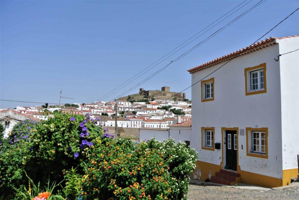 白壁の住宅の奥にメルトラ城を望む