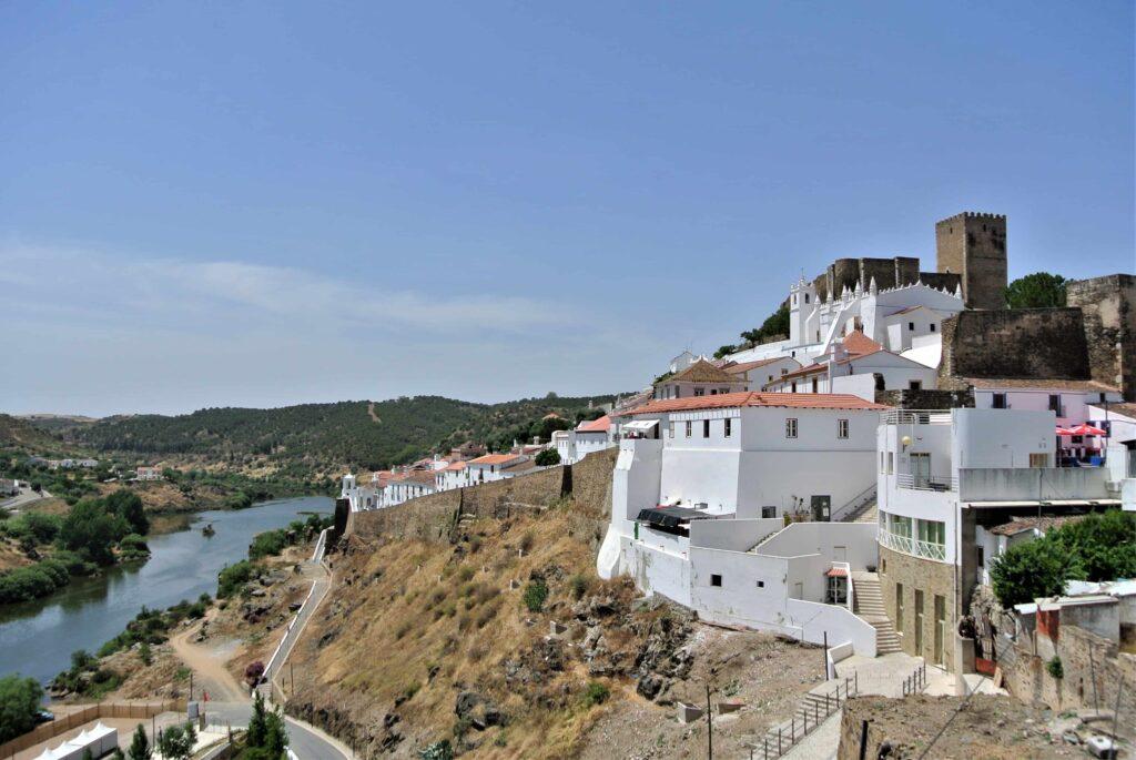 丘の上のメルトラ城と住宅、その脇に川が流れる