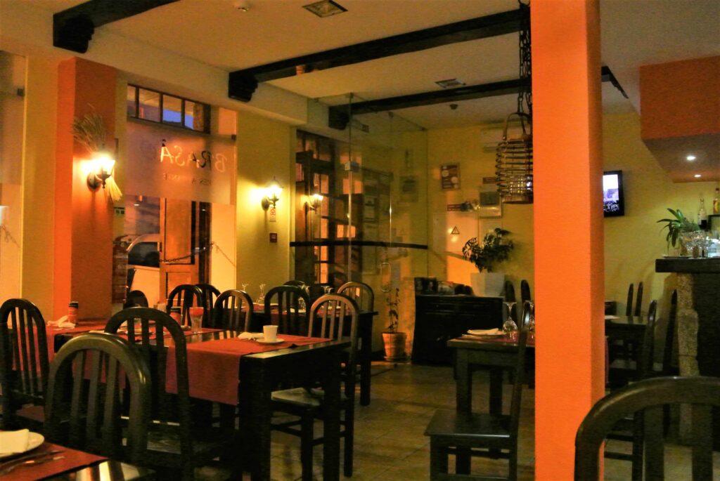 レストランO Brasao店内 オレンジ色の柱とオレンジ色のテーブルクロスの引かれた客席