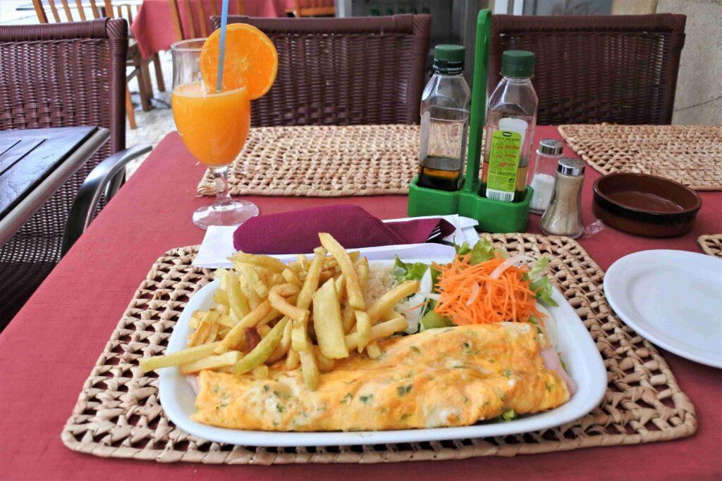 オムレツとフライドポテト、サラダのプレートとオレンジジュース