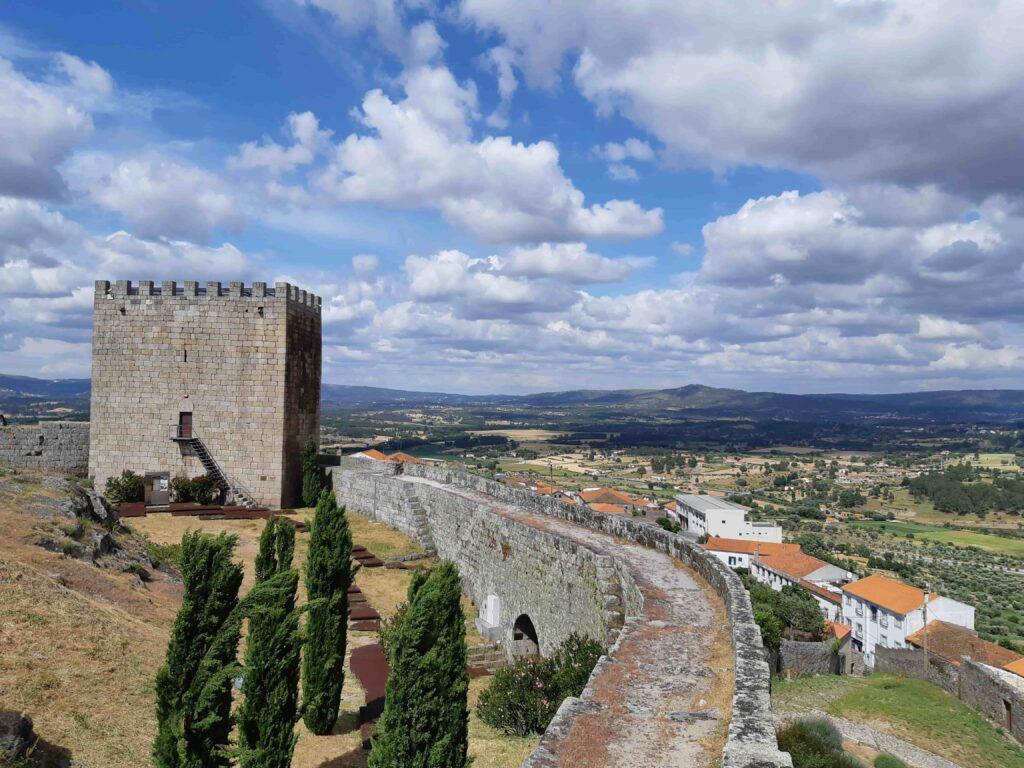 城壁上から見るセロリコ・ダ・ベイラ城の塔とその先に広がる農耕地帯