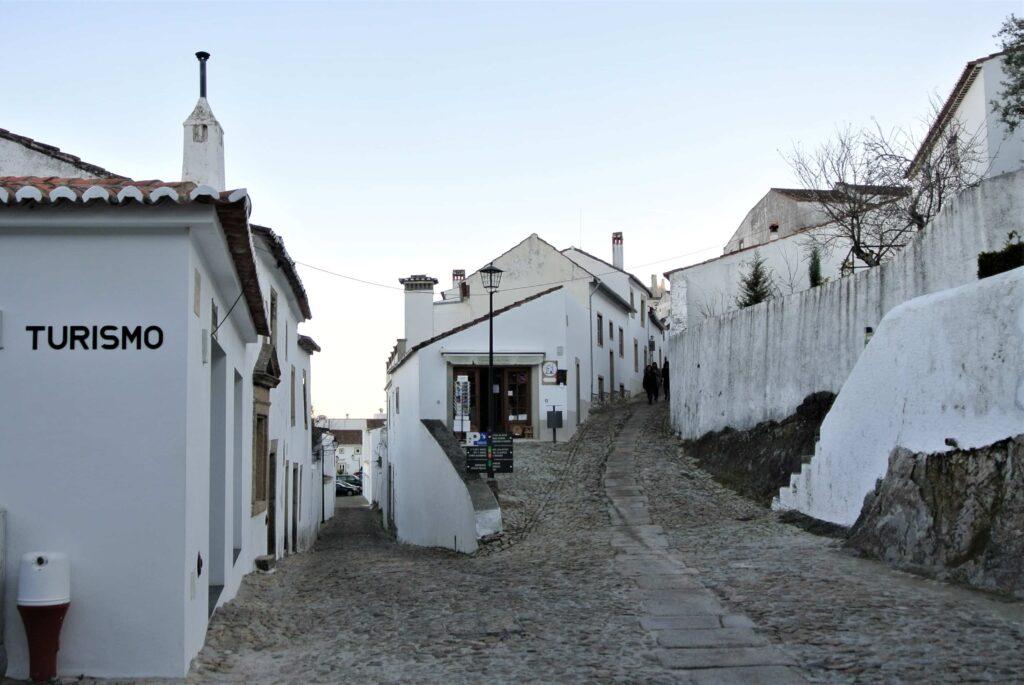 左にマルヴァン観光案内所の建物、奥は白い家々に囲まれた坂道