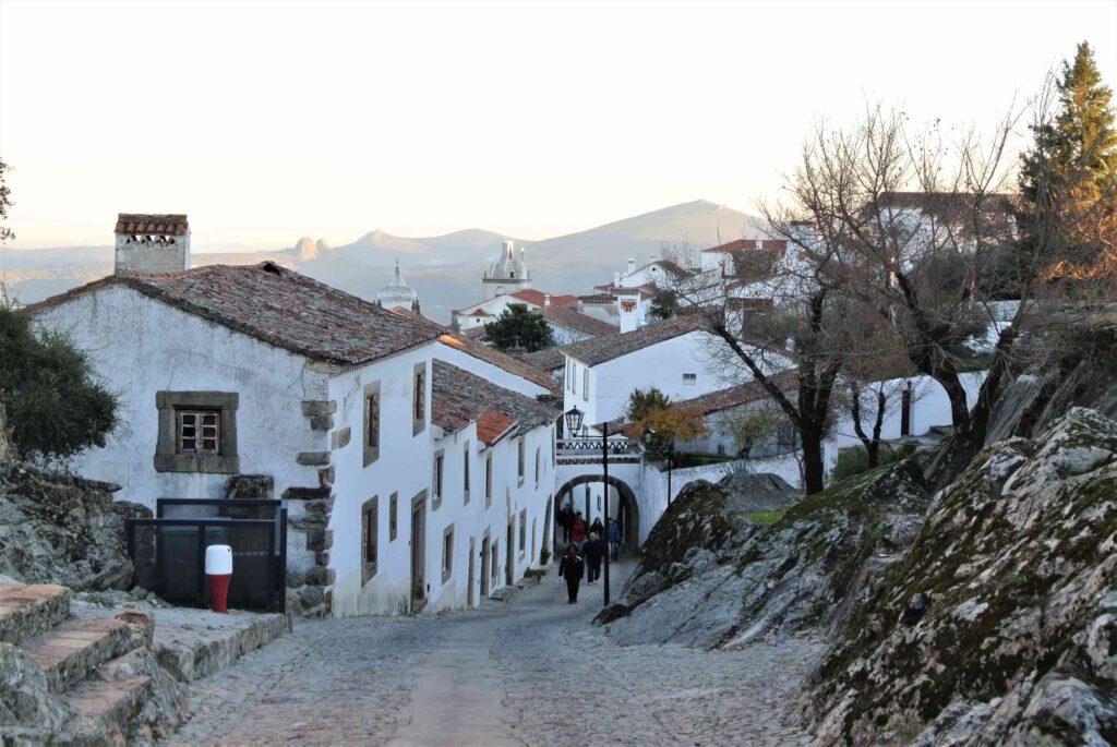 坂道の先に広がるマルヴァンの家々と教会 その先に夕暮れの山々