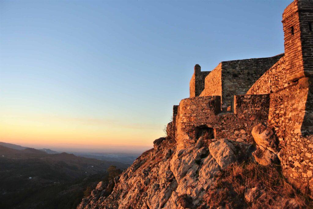 城壁とマルヴァン城の建つ山肌を夕日がオレンジに照らす